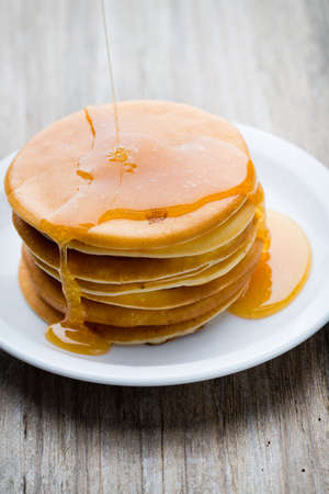 pancake: Stack of homemade pancakes with honey on wooden background. Stock Photo