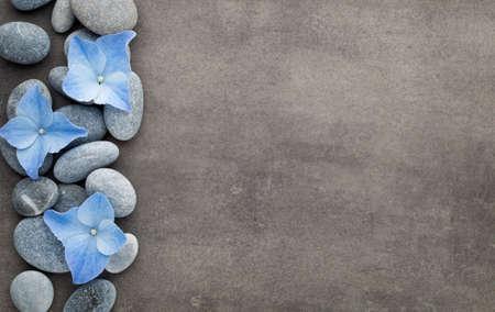 Spa Steine ??und Blumen auf grauem Hintergrund.