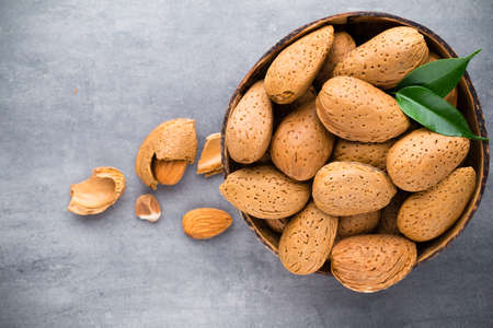 hard core: Group of almond nuts with leaves.Wooden background.