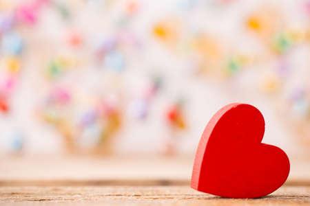Rode houten hart op een houten achtergrond met boke achtergrond.