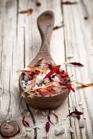 Homeopathic medicine; flower dry petals and spoon; wooden surface.