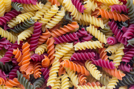 Eco macaroni pasta in a wooden bowl on a gray background. Stock Photo