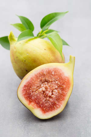 Whole figs and one fig sliced in half on top of a gray table.