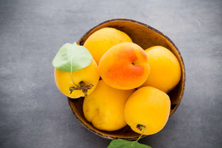 apricot kernels: Fresh apricots with leaves on the old wooden table. Stock Photo