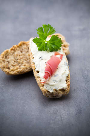 Rye crispbreads with soft cheese with herbs and bacon. Stock Photo