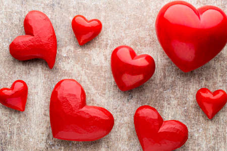 Hearts on the red color of the wood background. Stock Photo