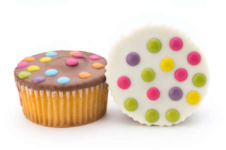 Cupcakes with colored candy on the white background.