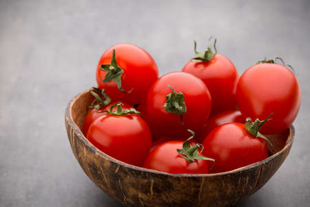 Cherry tomatoes. Three cherry tomatoes in a wooden bowl on a gray background. Stock Photo - 79385854