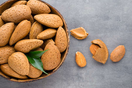 Group of almond nuts with leaves.Wooden background.