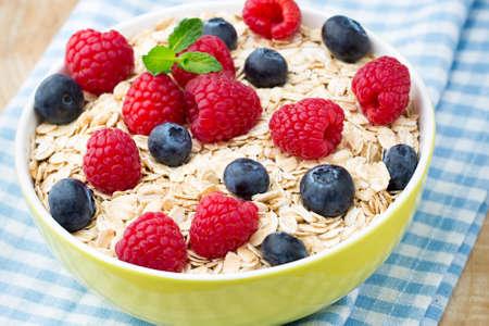 Oatmeal porridge with berries. Raspberries and blueberries.