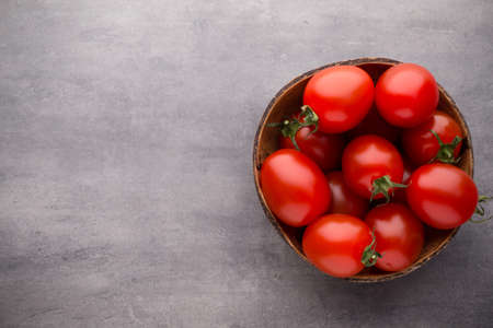 Cherry tomatoes. Three cherry tomatoes in a wooden bowl on a gray background.