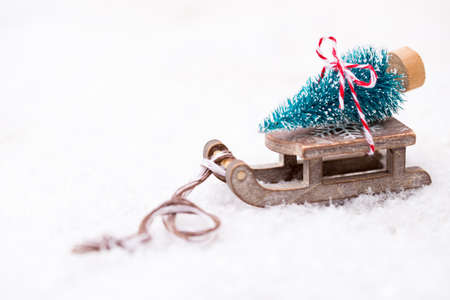 decorate: Christmas tree on the sled. Christmas and new year gold theme background.