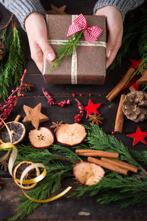 Woman holding Christmas presents laid on a wooden table background.