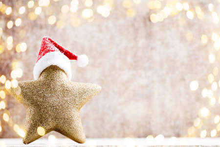 old desk: Christmas star with Santa hat. Vintages background. Stock Photo