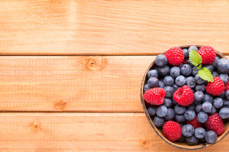 Juicy and fresh blueberries with green mint on rustic blue table. 写真素材