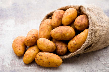 Bio rudy ziemniak drewniane tło.