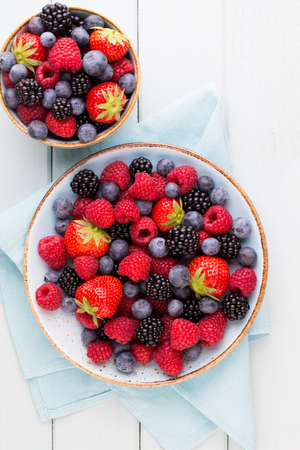Fresh berries salad in a plate on a  wooden background. Flat lay, top view, copy space. Foto de archivo