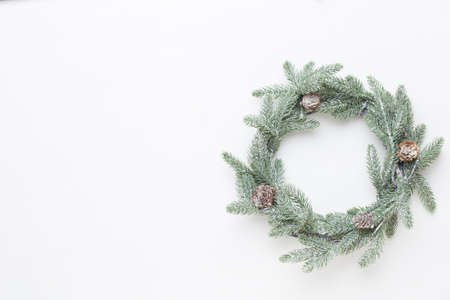 Christmas greeting card. Wreath decoration on white wooden background. New Year concept. Copy space.  Flat lay. Top view. Stock Photo