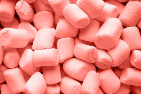 A pile of small living coral color puffy marshmallows.