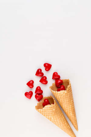 Creative composition for Valentines day with waffle cone, mixed hearts on white background top view. Fashion flat lay. Imagens