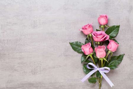 Flowers greeting card. Frame made of pink rose on gray background. Flat lay, top view, copy space. 版權商用圖片