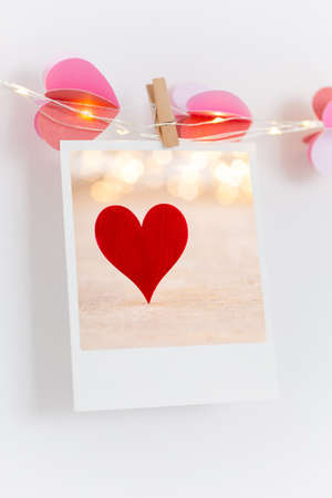 The polaroids photo red heart pinned on a lantern, white wall background. Standard-Bild - 116803051
