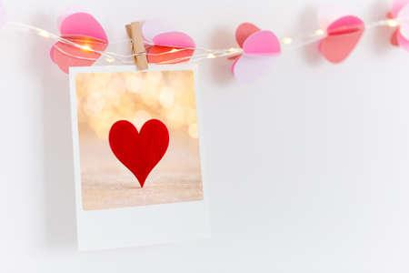 The polaroids photo red heart pinned on a lantern, white wall background. Standard-Bild - 116803028