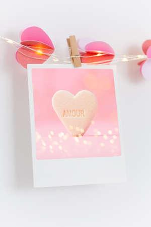 The polaroids photo red heart pinned on a lantern, white wall background. Standard-Bild - 117492761
