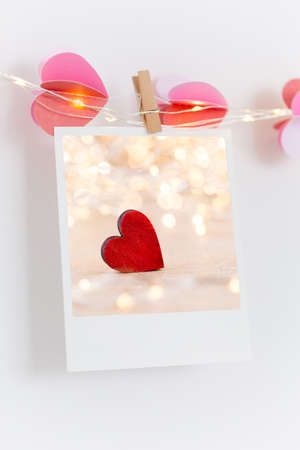 The polaroids photo red heart pinned on a lantern, white wall background.