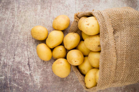 Sack of fresh raw potatoes on wooden background, top view.