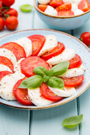 Tomatoes, mozzarella cheese, basil and spices on gray slate stone chalkboard