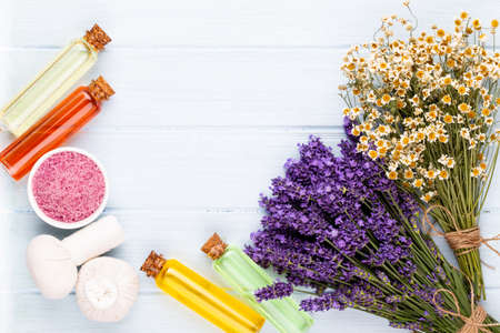 Essential oil and lavender, chamomile salt with flowers top view.
