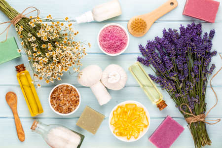 Essential oil and lavender, chamomile sea salt, spa,  with flowers top view.