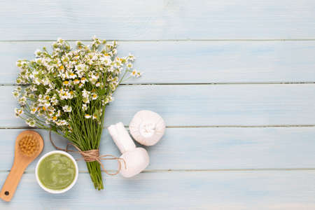 Spa aromatherapy background, flat lay of various beauty care products decorated with simple chamomile flowers. Фото со стока