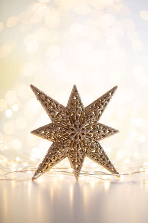 Christmas gold bokeh background with decorative star. Christmas gold stars. Christmas pattern. Background on the gray color. - Image Stock Photo