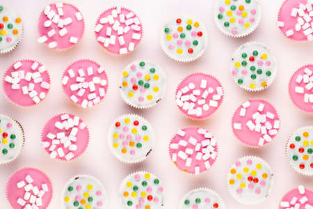 Multiple colorful nicely decorated muffins on a white background, top view. Reklamní fotografie - 128802182