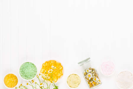 Composition aromatherapy with natural cosmetics and chamomile flowers on light background.