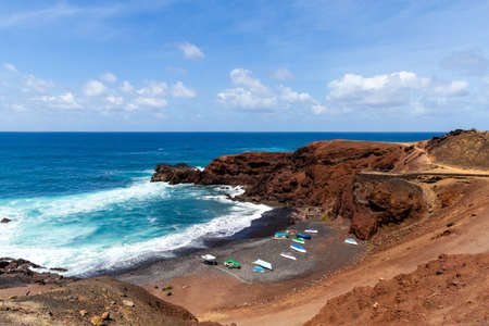 Beautiful beach on the island of Lanzarote. Sandy beach surrounded by volcanic mountains  Atlantic Ocean and wonderful beach. Lanzarote. Canary Islands Фото со стока