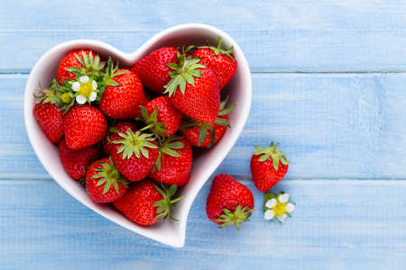 Strawberry heart. Fresh strawberries in plate on white wooden table. Top view, copy space. Stock Photo