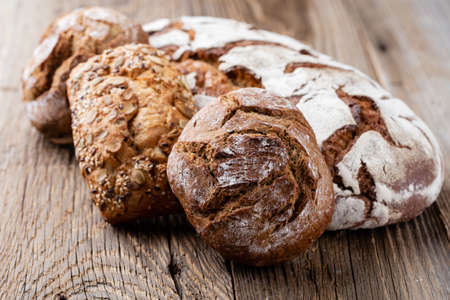 Bread background, top view of, black and rye loaves on black. Reklamní fotografie - 128677066