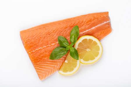 Rebanada de salmón rojo pescado con limón, albahaca aislado sobre fondo blanco. Vista superior. Endecha plana