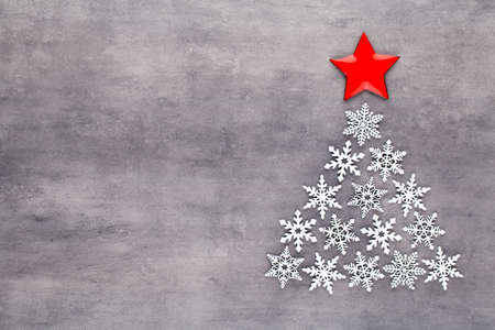 Christmas tree made from white snow flake decorations on gray  background with empty copy space for text. New year and christmas postcard. Reklamní fotografie
