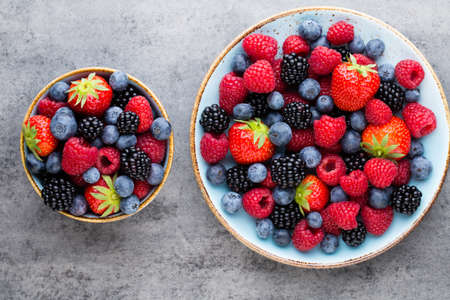 Fresh berries salad in a plate on a  wooden background. Flat lay, top view, copy space. Reklamní fotografie