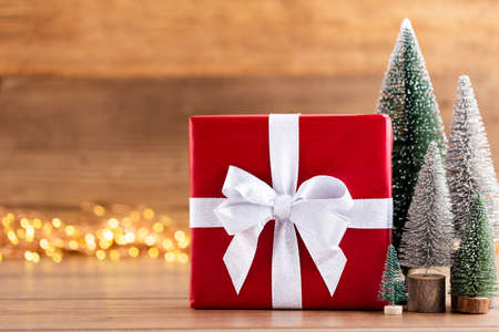 Christmas gift boxes with ribbons and tree on bokeh background. Standard-Bild - 130129818