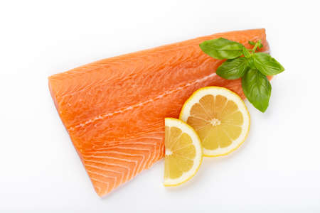 Slice of red fish salmon with lemon, basil isolated on white background. Top view. Flat lay
