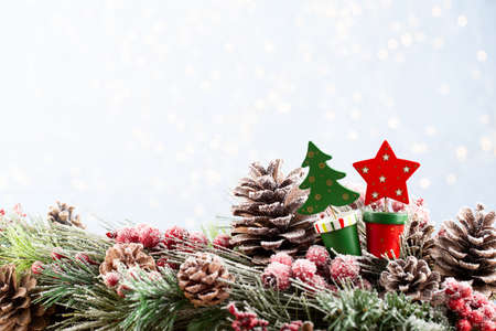 Christmas and New Year holidays bokeh background. Christmas Decoration Banner - Snowy Pine Cones On Fir Branch With Christmas Lights. Christmas bokeh background with snow fir tree. Top view with copy space for your text. Standard-Bild - 130129846