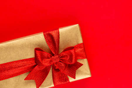 Top view of arranged wrapped christmas gift boxes with ribbons on red tabletop.