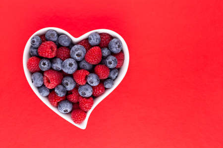 Blueberry and raspberries, fruit in a heart shaped dish on a porcelain bowl pastel background.