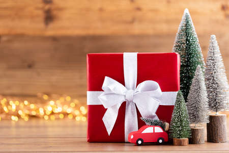 Christmas gift boxes with ribbons and tree on bokeh background. Stock Photo - 130812370