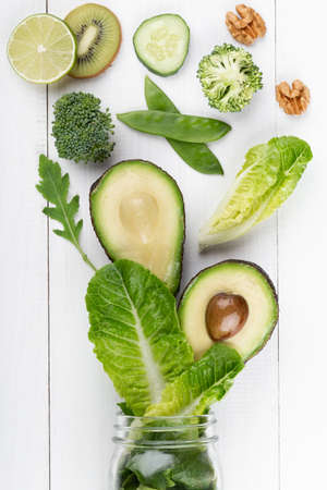 Glass jar mugs with green health vegetables lettuce leaves, lime, apple, kiwi, avocado, food concept.